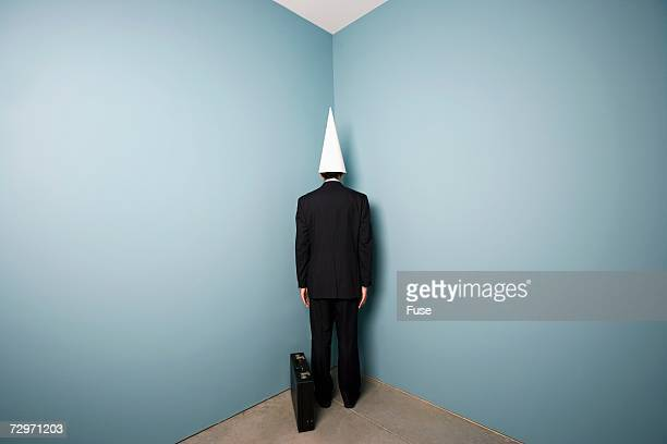 businessman wearing dunce cap standing in corner - dunce cap stock pictures, royalty-free photos & images