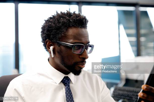 businessman wearing earbud headphones looking at a smartphone - multimedia stock pictures, royalty-free photos & images