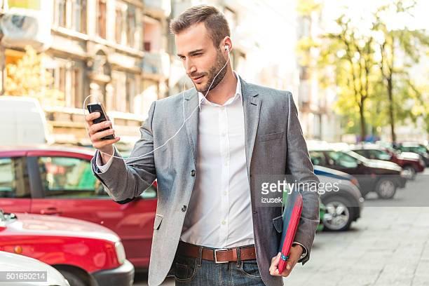 Businessman wearing earphone talking on smart phone on the street