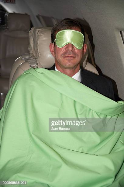 Businessman wearing eye mask and blanket on plane