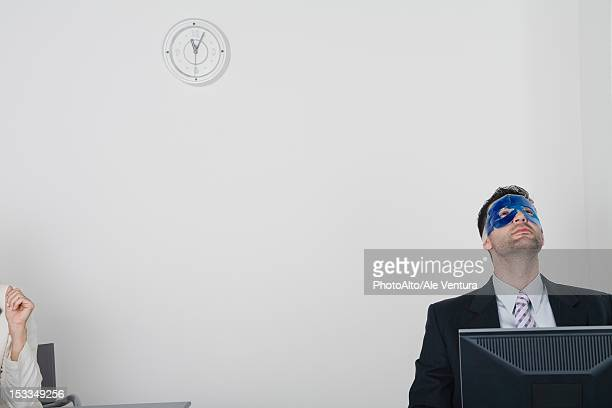 Businessman wearing eye mask