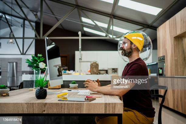 businessman wearing fishbowl while using computer at desk in modern office - avoidance stock pictures, royalty-free photos & images