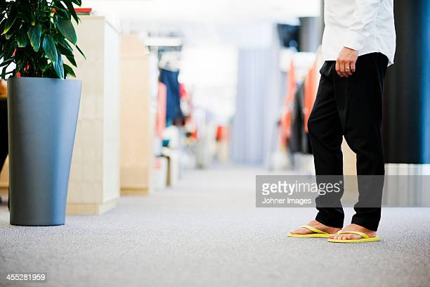 Businessman wearing flip-flops, low section