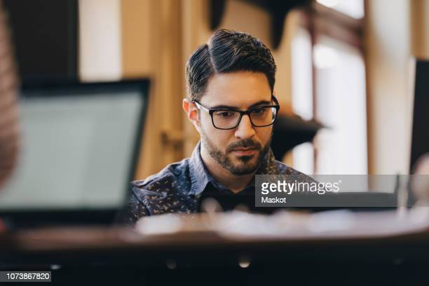 businessman wearing glasses while working in creative office - only mid adult men stock pictures, royalty-free photos & images