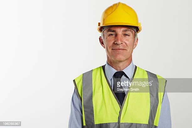 Businessman wearing hard hat and high vis jacket
