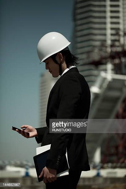 Businessman wearing hard hat&using mobile phone