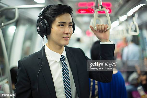Businessman wearing headphones on the train.