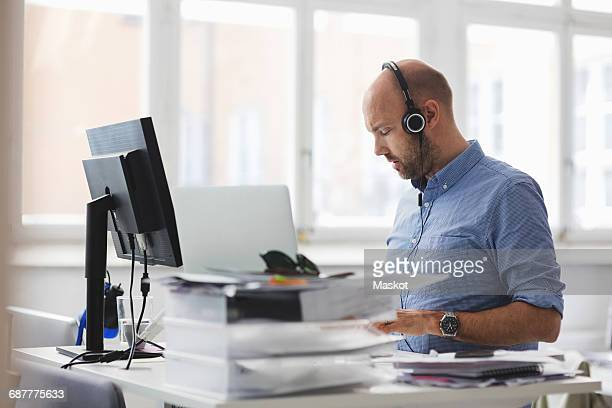 businessman wearing headphones working at desk in office - ergonomics stock photos and pictures