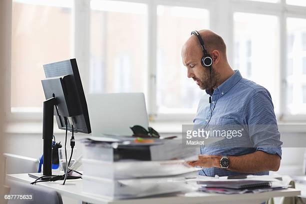 Businessman wearing headphones working at desk in office