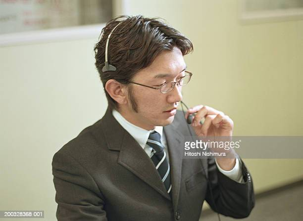 Businessman wearing headset in office, close-up
