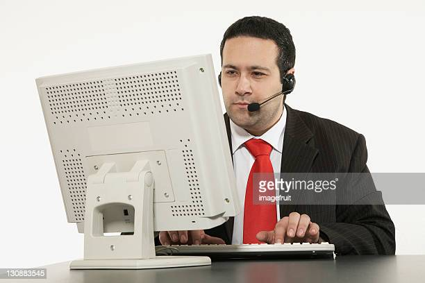 Businessman wearing headset sitting in front of computer