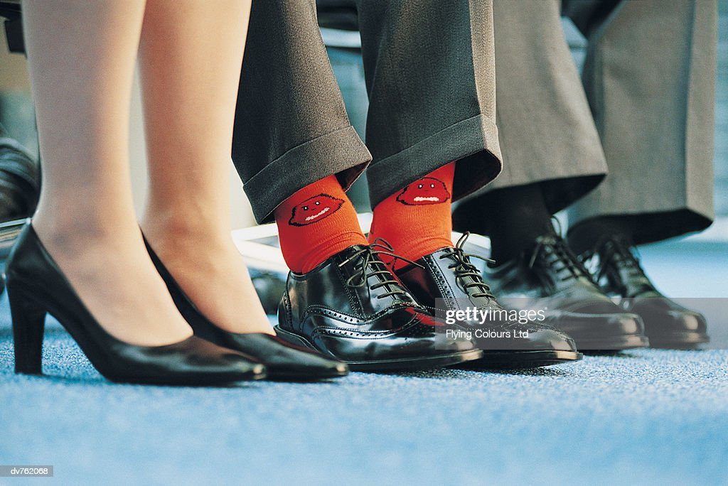 Businessman Wearing Individualistic Socks Between Two of His Colleagues : Stock Photo