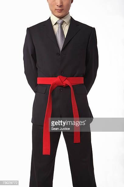 Businessman wearing martial arts belt, mid section