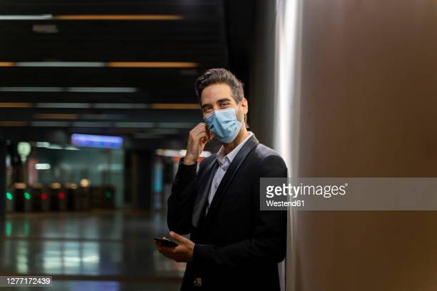 businessman wearing mask holding smart phone while standing by wall at station - obscured face stock pictures, royalty-free photos & images