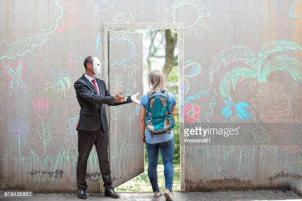 businessman wearing mask showing young woman way through concrete wall - multi colored suit stock photos and pictures