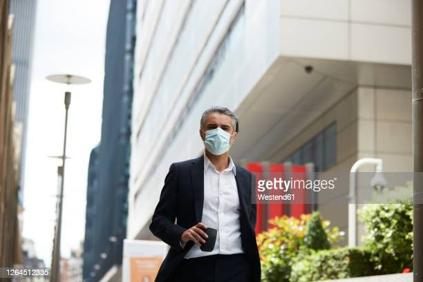 businessman wearing mask walking with cup in city - commuter stock pictures, royalty-free photos & images