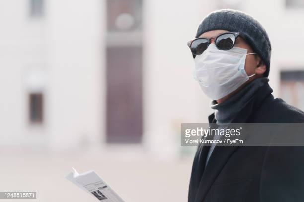 businessman wearing mask while standing in city - coronavirus winter stock pictures, royalty-free photos & images