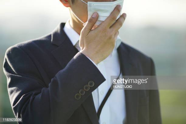 businessman wearing protective mask outdoors - influenza virus foto e immagini stock