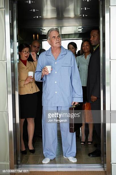 businessman wearing pyjamas standing in elevator, colleagues smiling in background - pyjama stockfoto's en -beelden