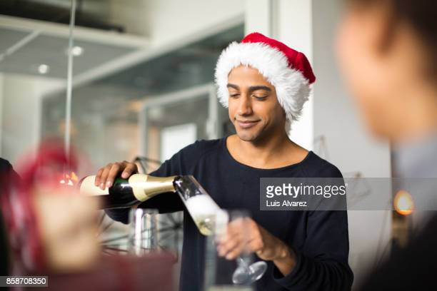 Businessman wearing Santa hat while pouring champagne into flute
