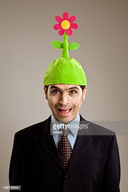 businessman wearing silly flower hat - izusek stock pictures, royalty-free photos & images
