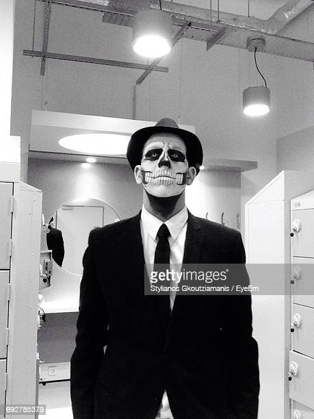 Businessman Wearing Skull Face Paint While Standing In Restroom