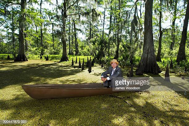Businessman wearing straw hat sitting in boat in swamp, portrait