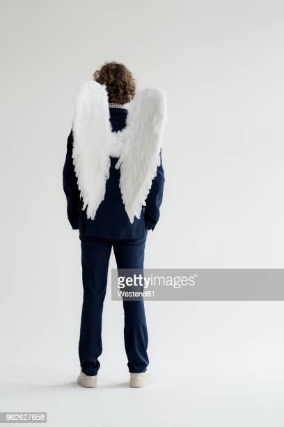 businessman wearing suit and angel's wings, rear view - aile d'animal photos et images de collection