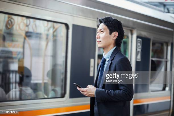 Businessman wearing suit standing at train station platform, holding mobile phone.