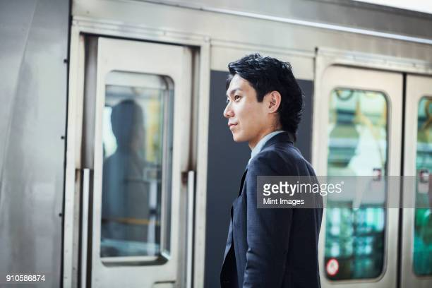 businessman wearing suit standing at train station platform. - 通勤 ストックフォトと画像