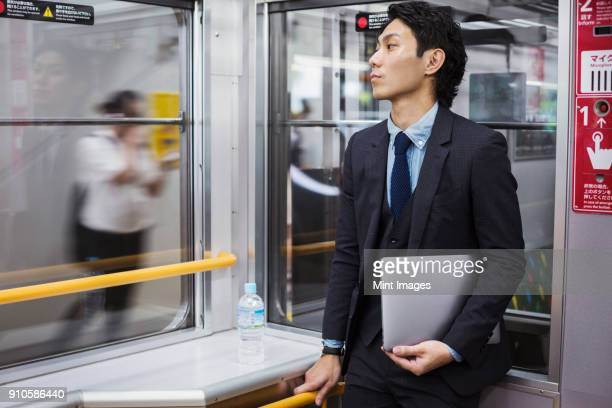 businessman wearing suit standing on a commuter train, holding laptop. - 通勤電車 ストックフォトと画像