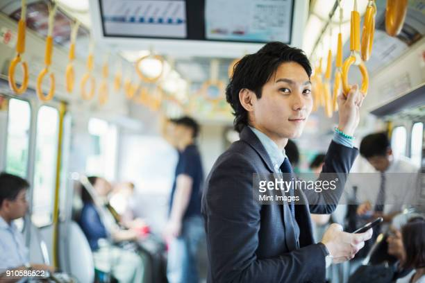 Businessman wearing suit standing on a commuter train, holding mobile phone.