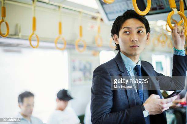 businessman wearing suit standing on a commuter train, holding mobile phone. - 通勤電車 ストックフォトと画像