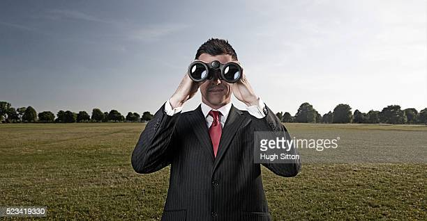 businessman wearing suit, using binoculars standing outside - hugh sitton stock pictures, royalty-free photos & images
