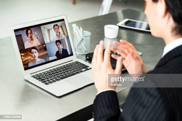 スーツを着たビジネスマンがオフィスでオンライン会議をしています - 離れた ストックフォトと画像