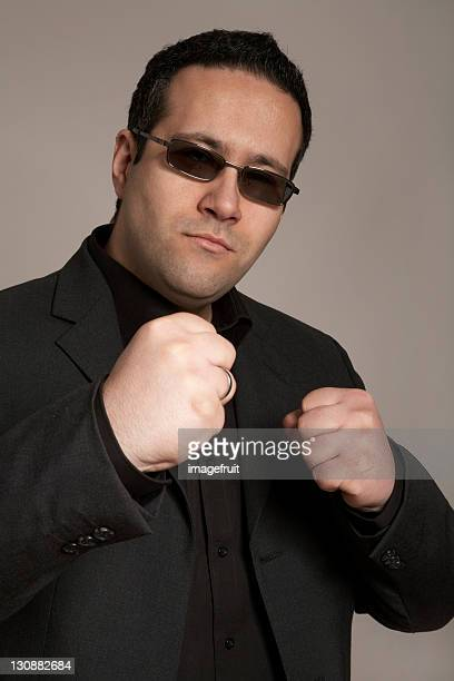 Businessman wearing sunglasses ready for a fight