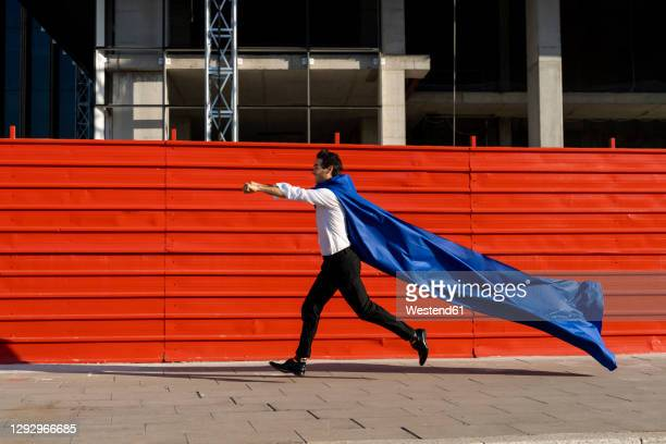 businessman wearing superhero cape running on pavement - cape stock pictures, royalty-free photos & images