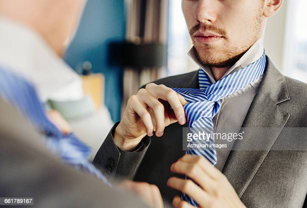 businessman wearing tie in front of mirror at hotel room - striped suit stock pictures, royalty-free photos & images