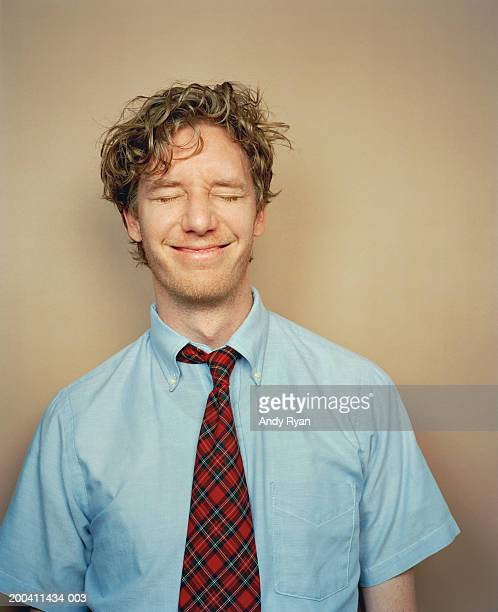 Businessman wearing tie with eyes closed, smiling