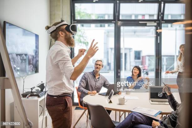 Businessman wearing virtual reality headset giving presentation to team