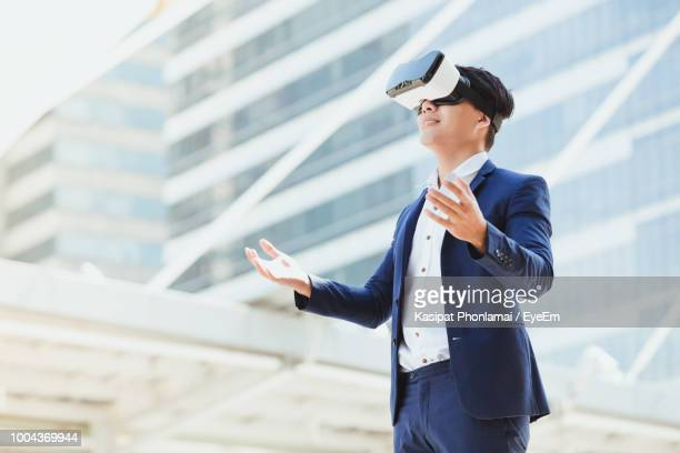 Businessman Wearing Virtual Reality Simulator Against Office Building
