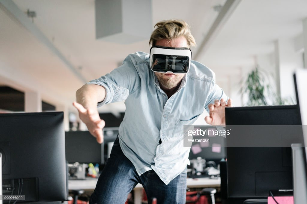 Businessman wearing VR glasses in office : ストックフォト