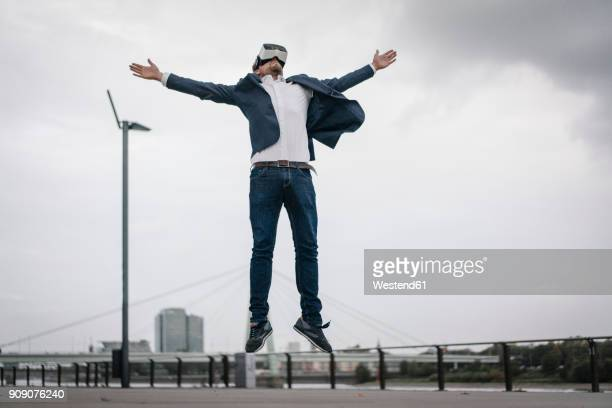 businessman wearing vr glasses jumping in the city - stir crazy stock photos and pictures