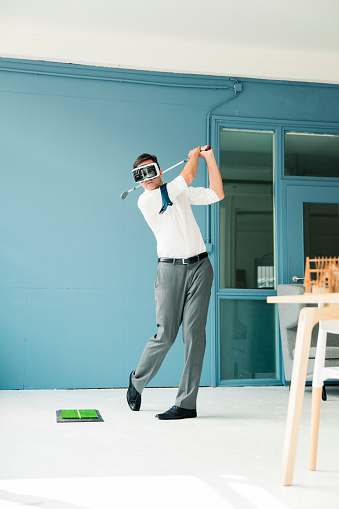 Businessman wearing VR glasses playing golf in office - gettyimageskorea
