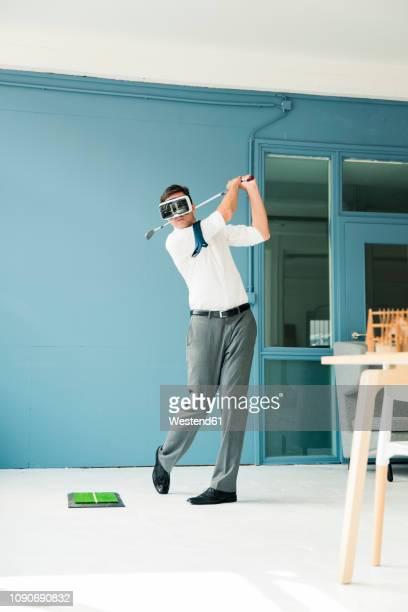 businessman wearing vr glasses playing golf in office - golf sport stockfoto's en -beelden