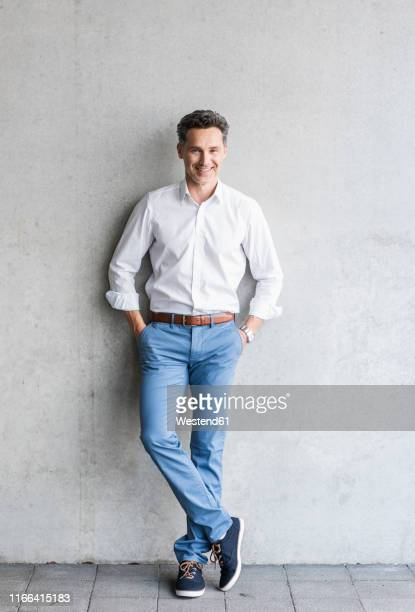 businessman wearing white shirt, grey wall in the background - lässige kleidung stock-fotos und bilder