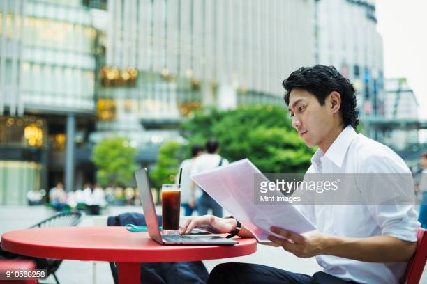 businessman wearing white shirt sitting outdoors at red table, holding papers, working on laptop. - 白いシャツ ストックフォトと画像