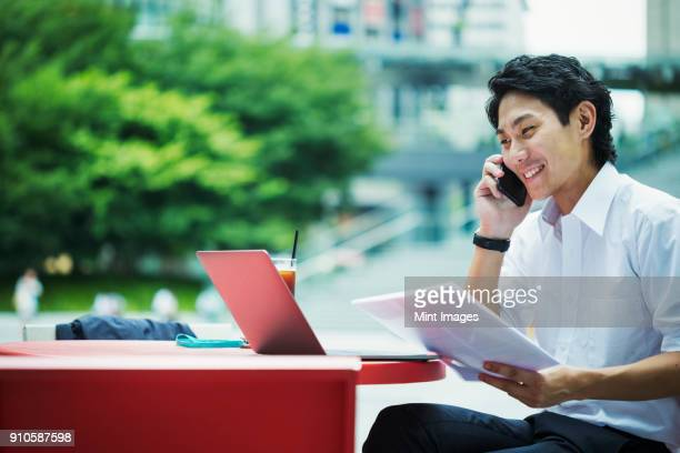 Businessman wearing white shirt sitting outdoors at red table, holding papers, using mobile phone.
