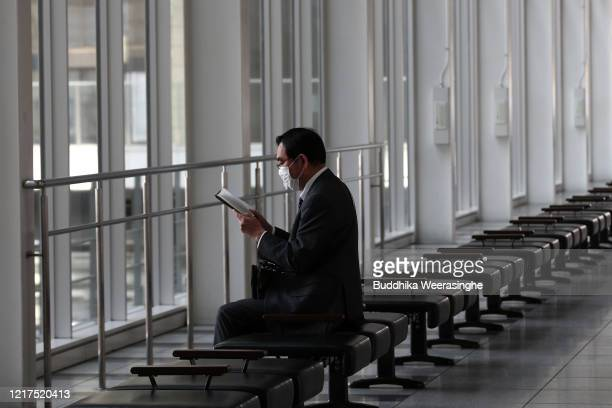 Businessman wears a face mask as he reads a book along a row of empty seats on April 8, 2020 in Osaka, Japan. Japans Prime Minister, Shinzo Abe,...