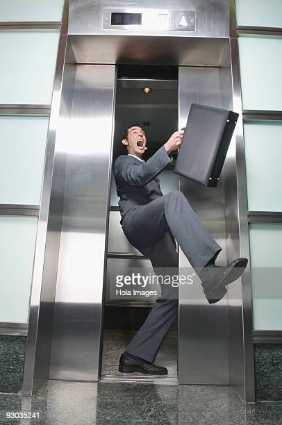 Businessman wedged between elevator doors